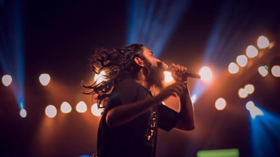 A singer with long hair and a beard, wearing headphones and raising his arm, in front of a backdrop of spotlights.