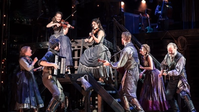 Seven performers with violins, guitars, and an accordion on stage