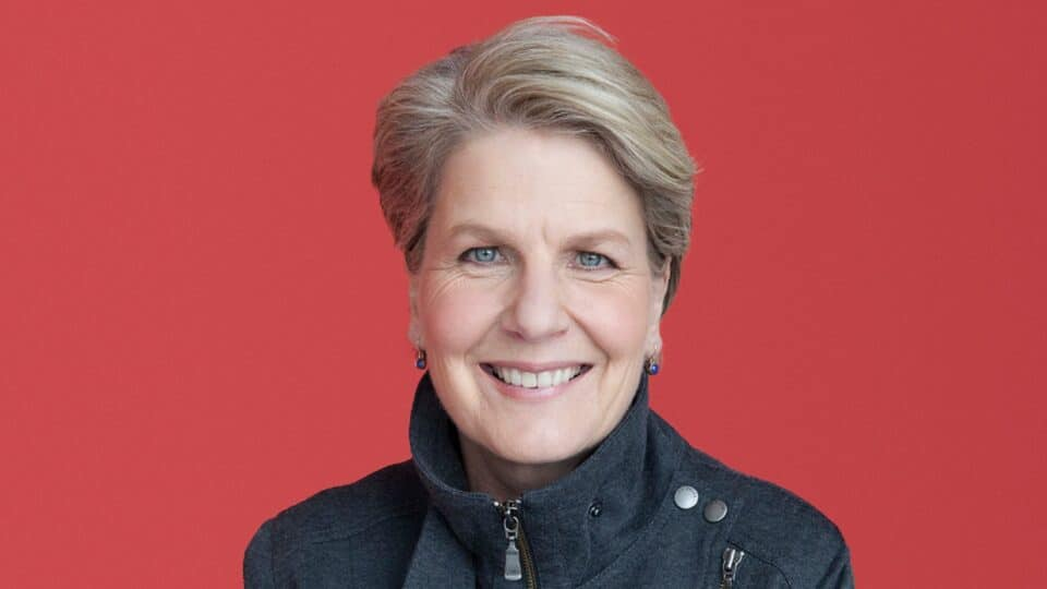 A head and shoulders photograph of Sandi Toksvig smiling, wearing a dark blue coat, in front of a red background.