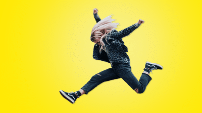 A child dressed in ripped jeans and a leopard print jacket jumps into the air in front of a yellow background.