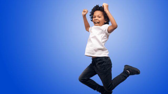 5-10s MYC photo - boy jumping excitedly on blue background