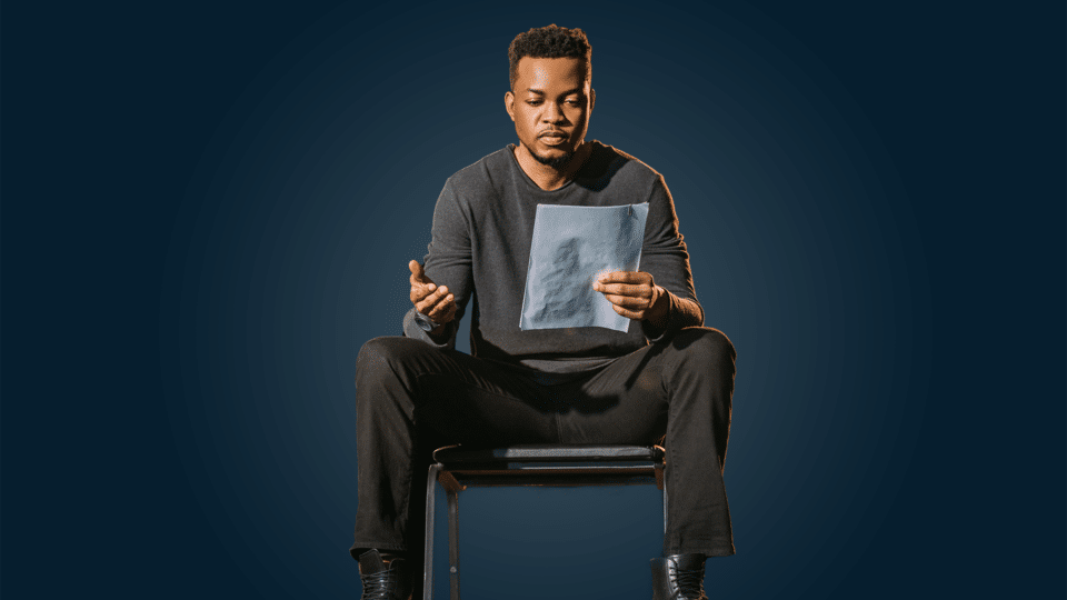 Acting 101 - photo of a man sat down reading a script on a navy blue background