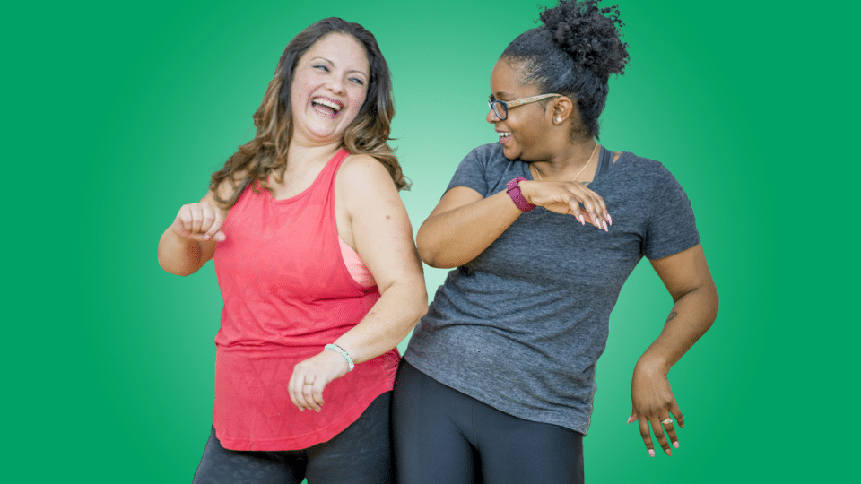 Musical Theatre Dance - two women dancing together and laughing with a green background.