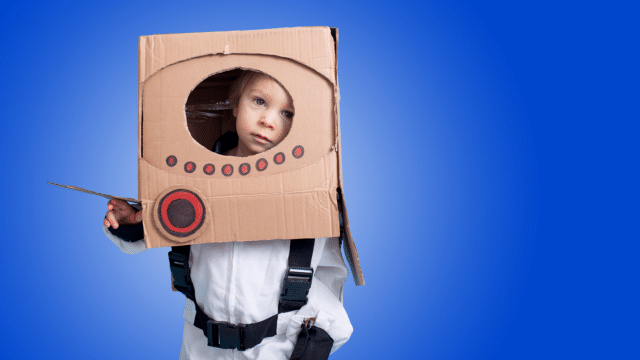 Tots Stars - photo of a young boy dressed as a space ship with a cardboard box on his head on a blue coloured background.