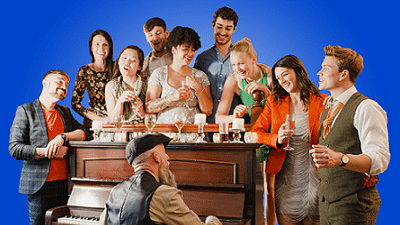 Family Sing-a-long - Photo of a large group of people around a piano, singing, with a man sitting playing